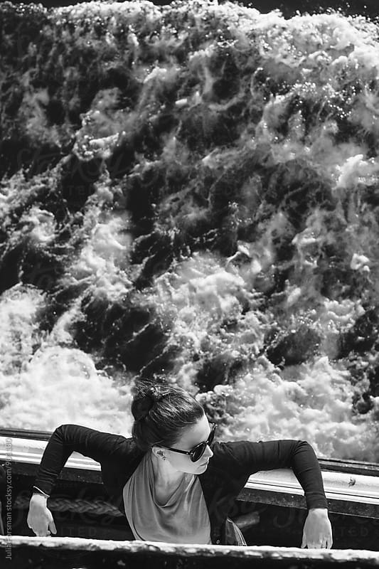 Beautiful young woman leans against the rails of a ferryboat. Behind her is the sea. by Julia Forsman for Stocksy United
