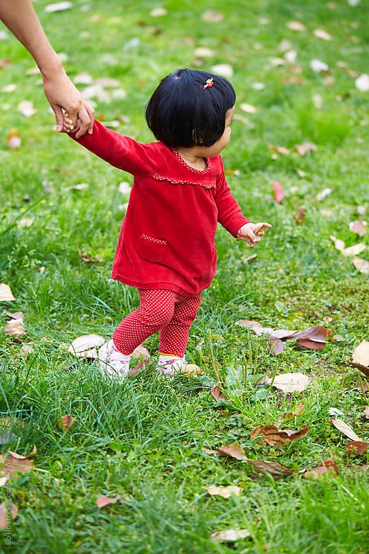 baby girl learning to walk by Bo Bo for Stocksy United