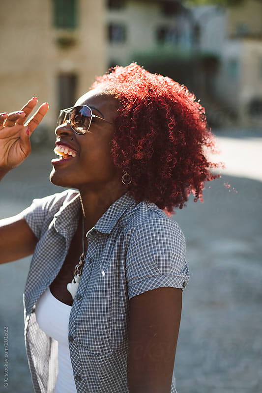 Happy black young woman laughing outdoors by GIC for Stocksy United