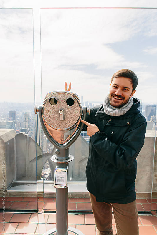 Happy man gesturing at Empire State building by Alejandro Moreno de Carlos for Stocksy United