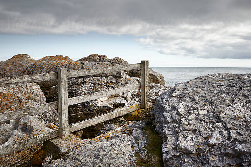 A fence separating land by the sea by James Ross for Stocksy United