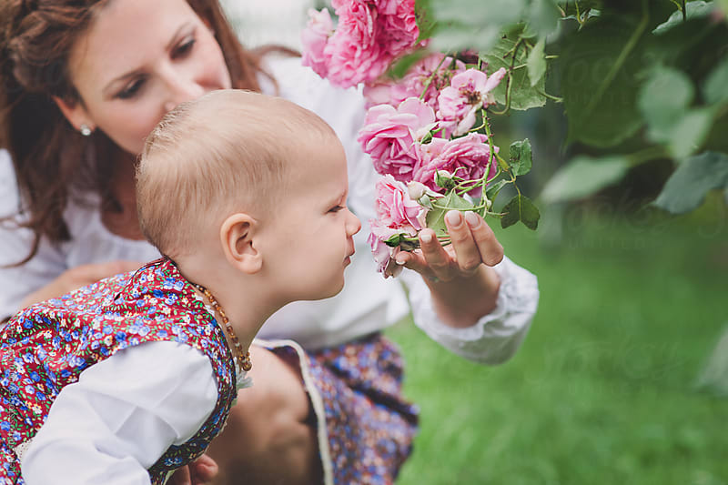 Little girl with her mother smelling roses by Lea Csontos for Stocksy United