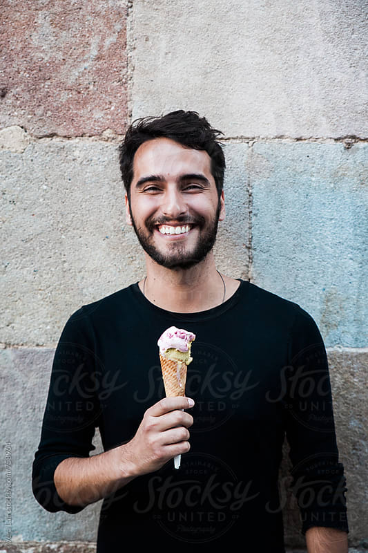 Smilling man with a ice cream cone by Vera Lair for Stocksy United