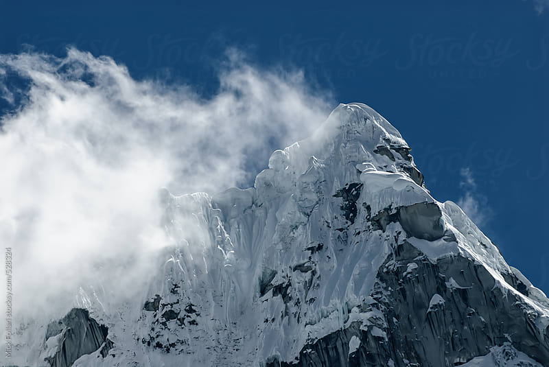 Dramatic icy mountain summit with cornices and steep couloirs by Mick Follari for Stocksy United