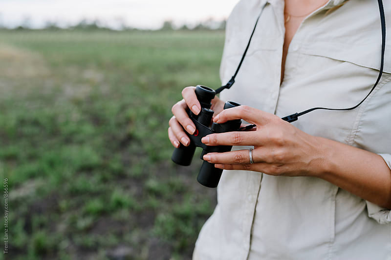 Close-up of woman's hands holding binoculars in African safari by Trent Lanz for Stocksy United