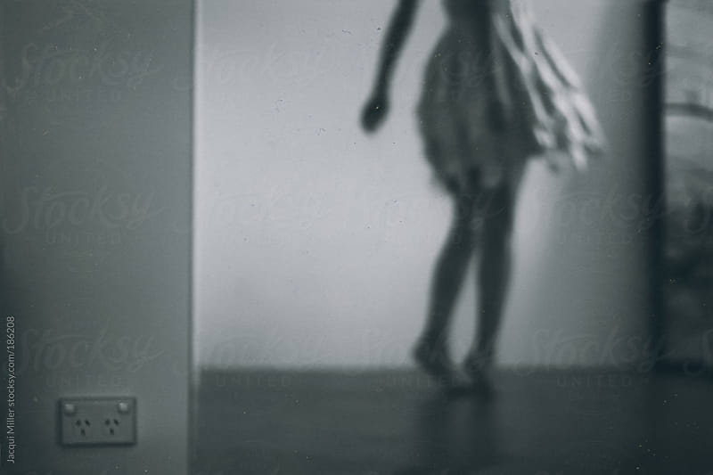 Woman wearing a flowing skirt twirls alone in her home by Jacqui Miller for Stocksy United