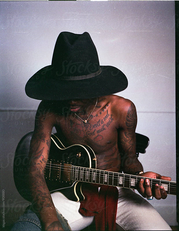 Stylish tatooed black model with hat photographed on 120 roll film by kkgas for Stocksy United