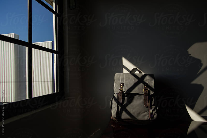 Book bag sitting in window light in a hotel by Eddie Pearson for Stocksy United