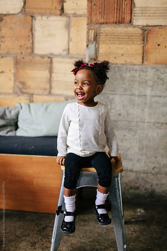 A natural light portrait of an adorable 2 year old sitting on a stool by Kristen Curette Hines for Stocksy United
