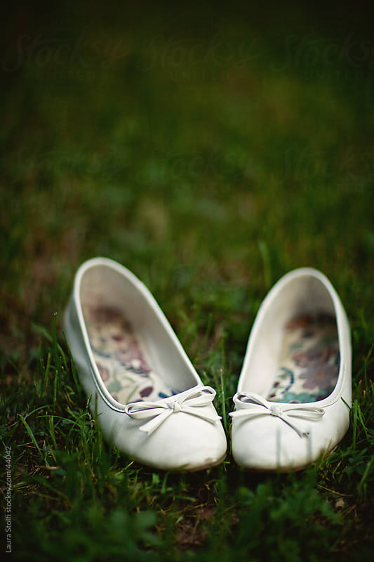 White bridal flat shoes in grass by Laura Stolfi for Stocksy United