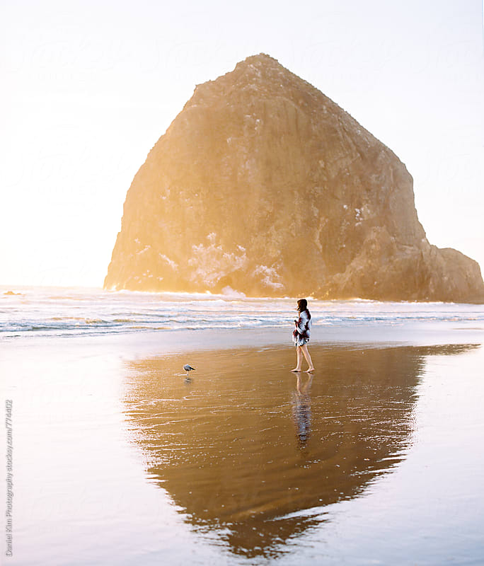 Woman walking along coast by Daniel Kim Photography for Stocksy United