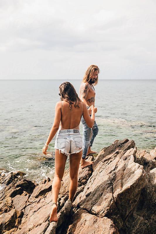 Beautiful couple climbing the rocks on the beach