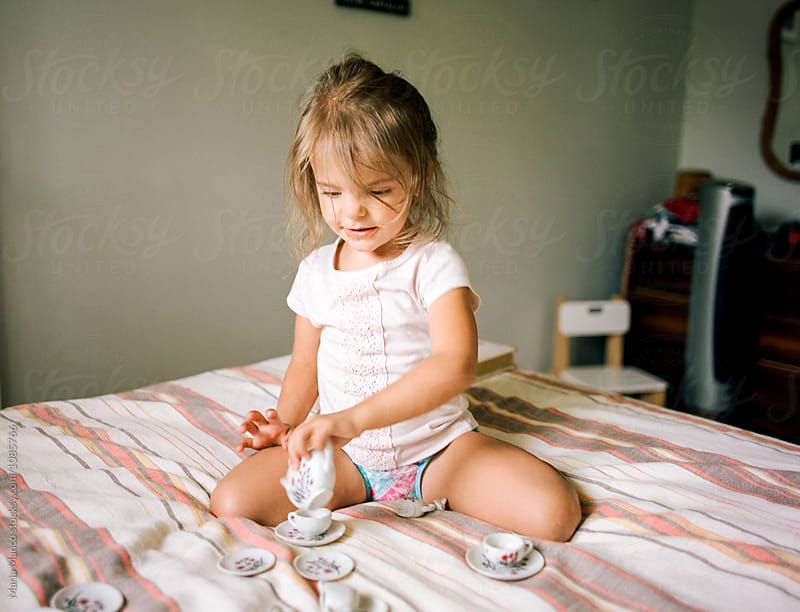 little girls pours a cup of tea by Maria Manco for Stocksy United