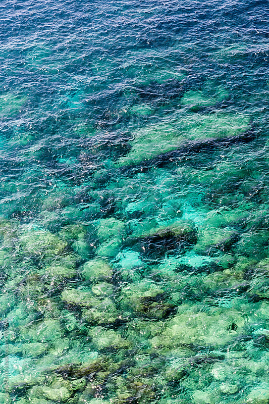 Aerial view of rocks in emerald water by Luca Pierro for Stocksy United