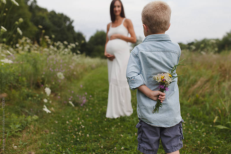 A boy hiding a bouquet of wildflowers behind his back for his pregnant mother by Amanda Worrall for Stocksy United
