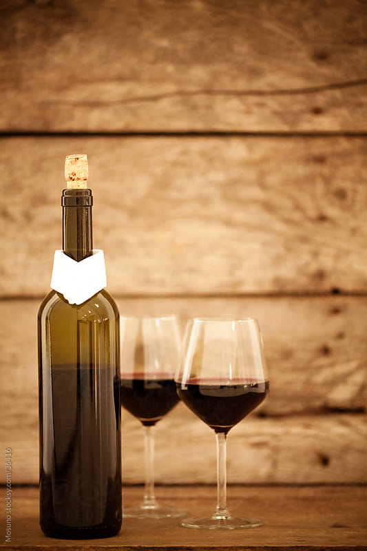 Two glasses of wine and a bottle on a wooden table. by Mosuno for Stocksy United