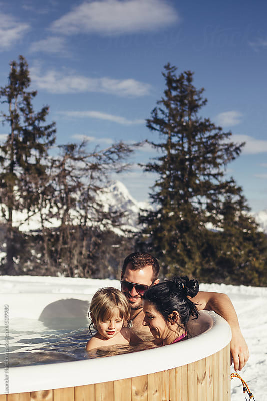 young family in outdoor jacuzzi in alpine winter landscape by Leander Nardin for Stocksy United