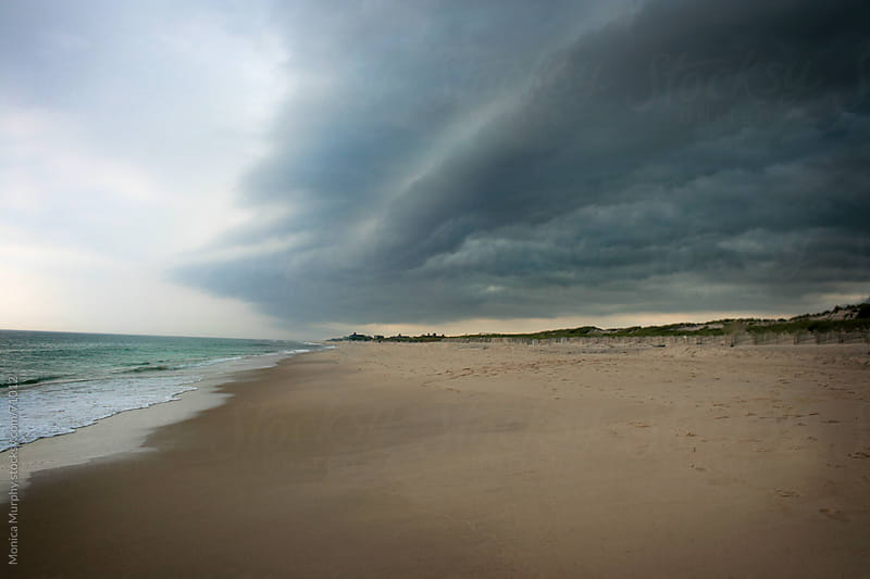 Storm clouds rolling in over the beach by Monica Murphy for Stocksy United