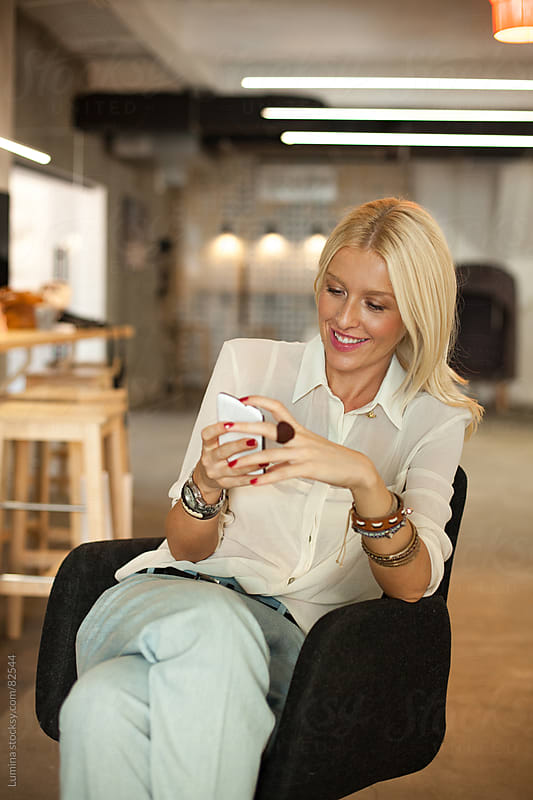 Smiling Businesswoman Using Mobile Phone by Lumina for Stocksy United