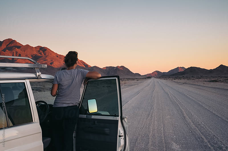 Woman on a road trip through the desert leaning out of her car watching a sunset by Micky Wiswedel for Stocksy United