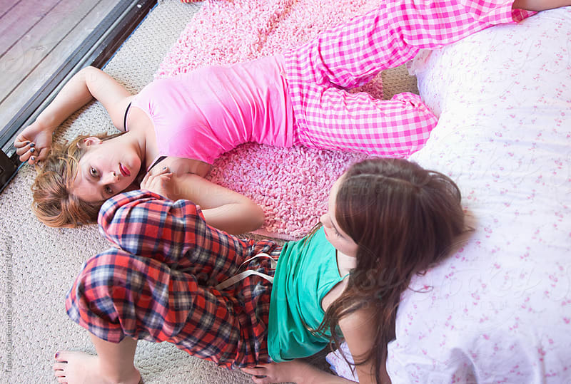 two tweens relaxing on the floor by Tanya Constantine for Stocksy United