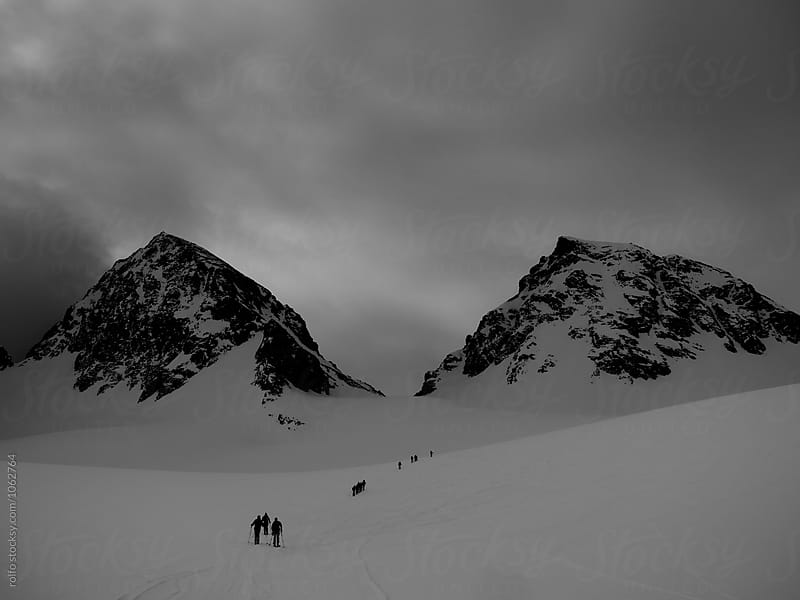 Group of alpinists walking towards two rocky peaks by rolfo for Stocksy United