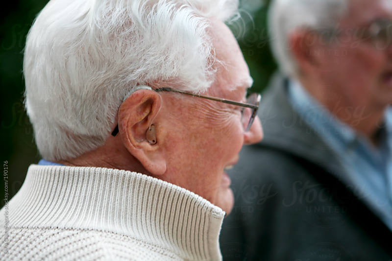 Elderly gray haired man showing profile and hearing aid by Dina Giangregorio for Stocksy United