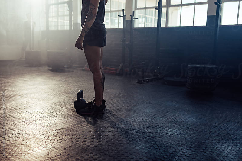 Woman standing with a kettle bell on gym floor by Jacob Lund for Stocksy United