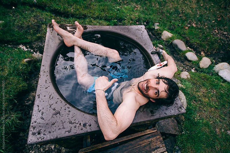 Young man bathing on a small hot tub by Alejandro Moreno de Carlos for Stocksy United