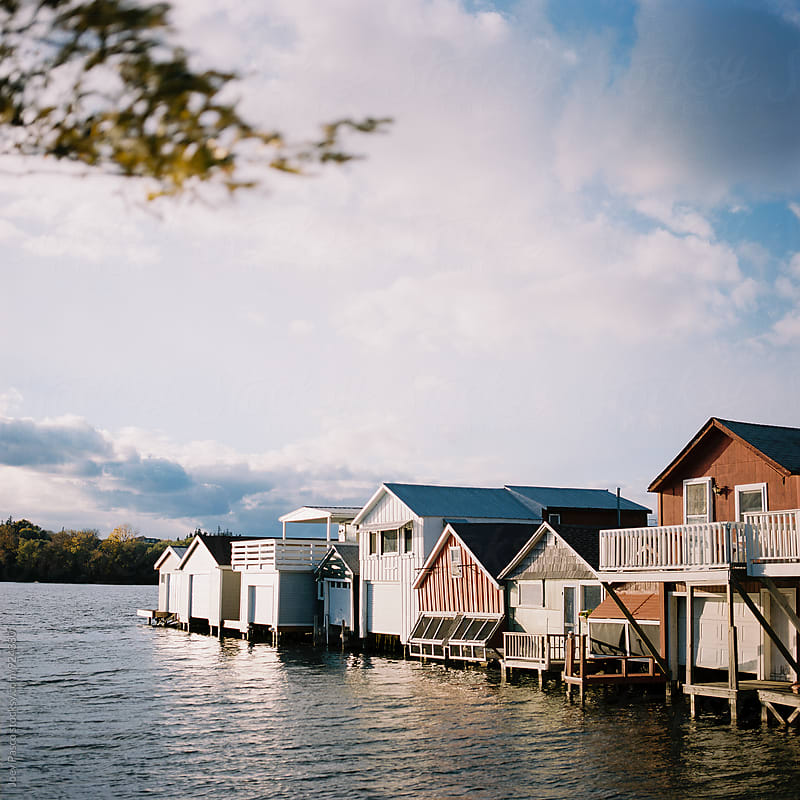 Colorful boathouses at sunset on Lake Canandaigua by Joey Pasco for Stocksy United