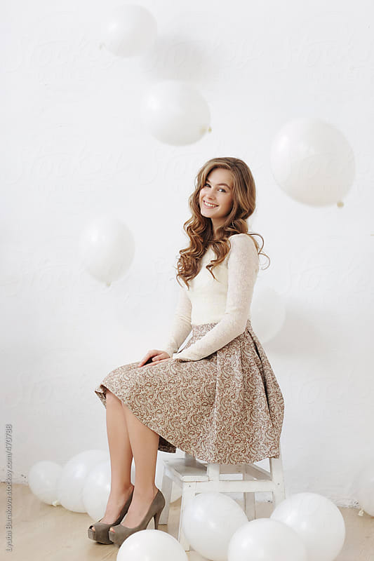 Beautiful young woman among white balloons by Lyuba Burakova for Stocksy United