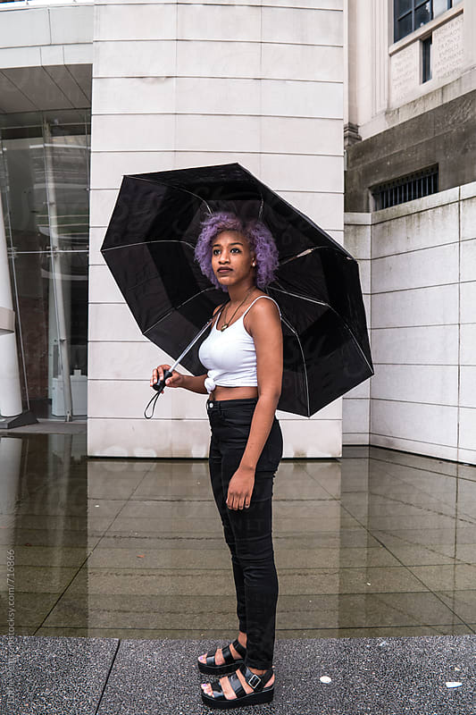Pretty young woman standing with her umbrella by Eddie Pearson for Stocksy United