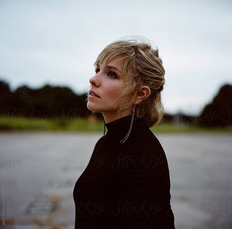 Moody portrait of a beautiful woman in an abandoned parking lot by Jakob for Stocksy United