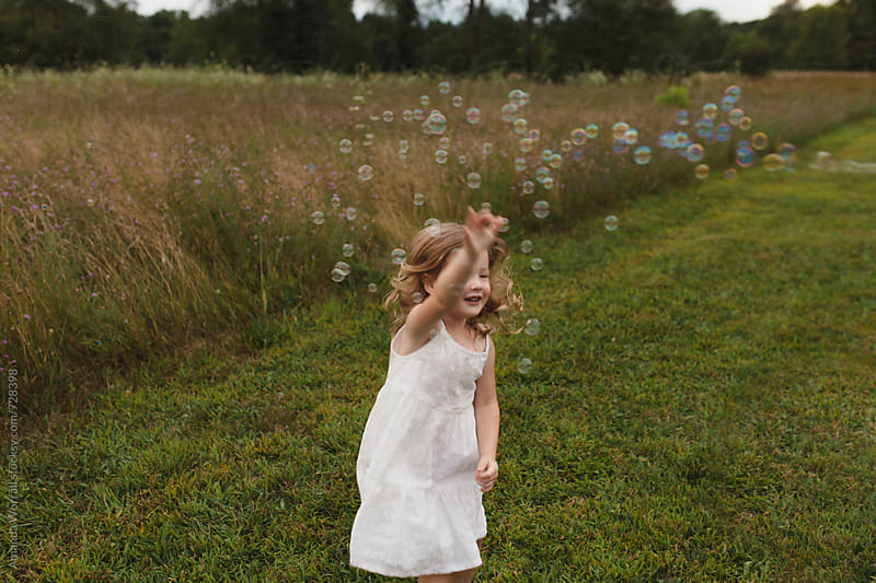 Young girl running through field, chasing bubbles by Amanda Worrall for Stocksy United