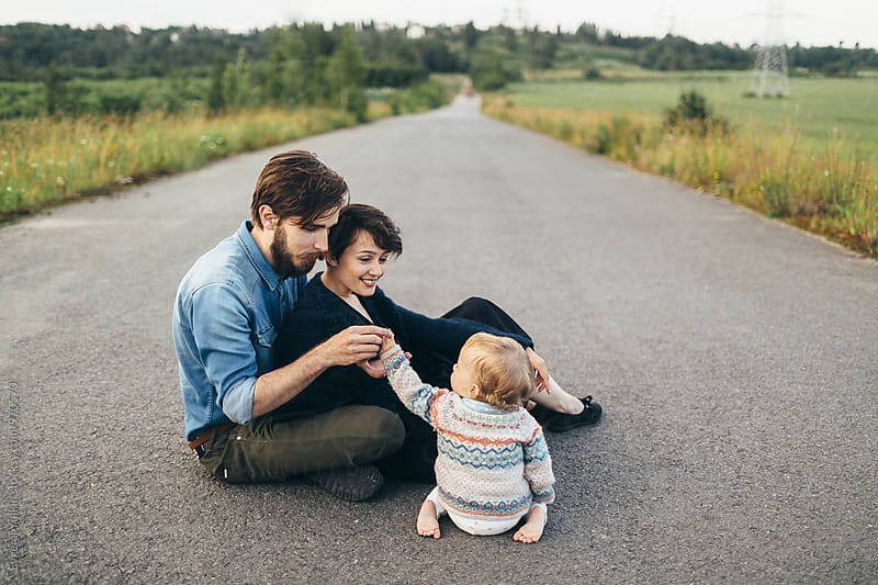 Parents with their baby girl sitting on the road by Evgenij Yulkin for Stocksy United