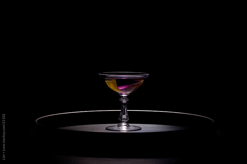 Purple cocktail on round tray by Lior + Lone for Stocksy United