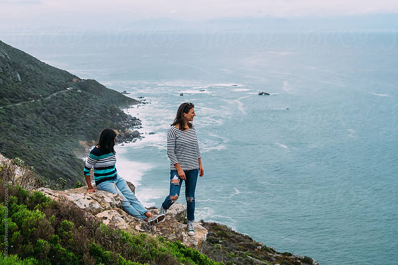 Friends on a mountain side overlooking the the ocean by Micky Wiswedel for Stocksy United