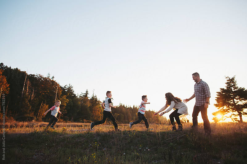 Young boys running to mom and dad - outside at sunset by Rob and Julia Campbell for Stocksy United