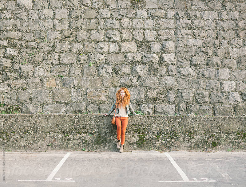 Ginger Woman Against a Stone Wall by Lumina for Stocksy United