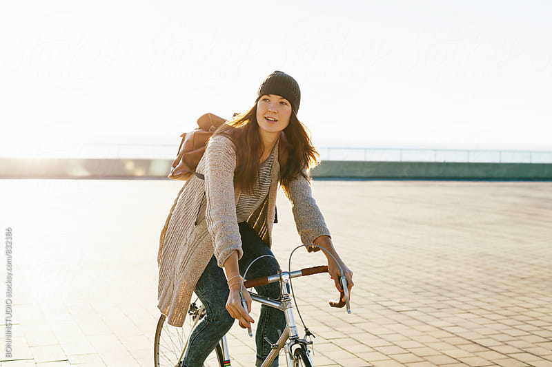 Woman riding her vintage bicycle in the city. by BONNINSTUDIO for Stocksy United