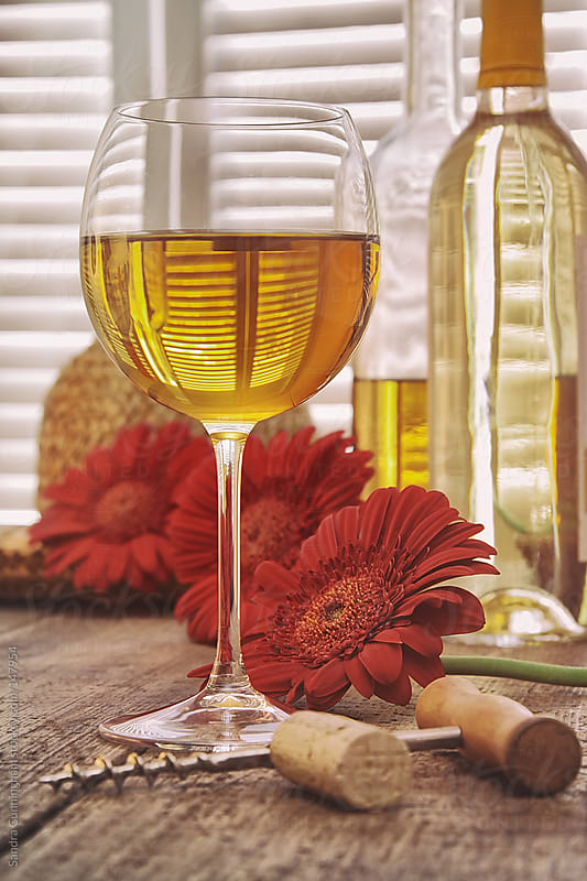 Glass of white wine with flowers in a sun filled room by Sandra Cunningham for Stocksy United