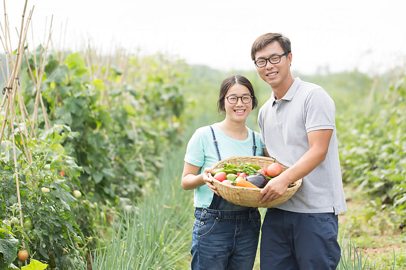 Young Chinese farm workers with vegetables grown on farm by Maa Hoo for Stocksy United
