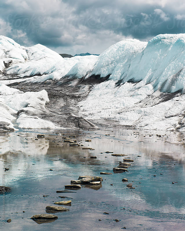 stepping stones leading across a shallow icy pool of a glacier by Tara Romasanta for Stocksy United