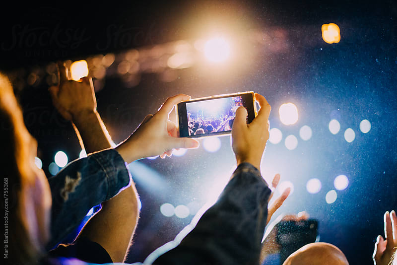 Taking a picture from the crowd with an smartphone in a music show by María Barba for Stocksy United