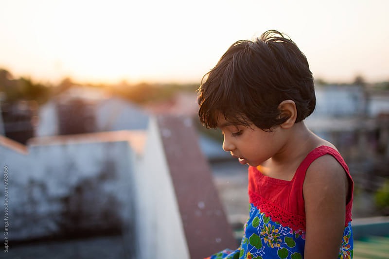 Cute little girl sitting on rooftop at sunset in a pensive mood by Saptak Ganguly for Stocksy United