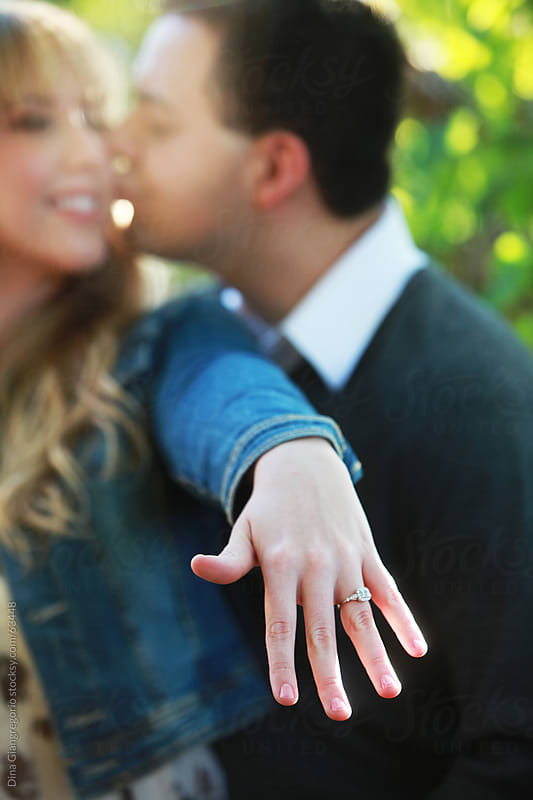 Male kissing female, her hand in focus showing ring  in foreground, faces blurred in background by Dina Giangregorio for Stocksy United