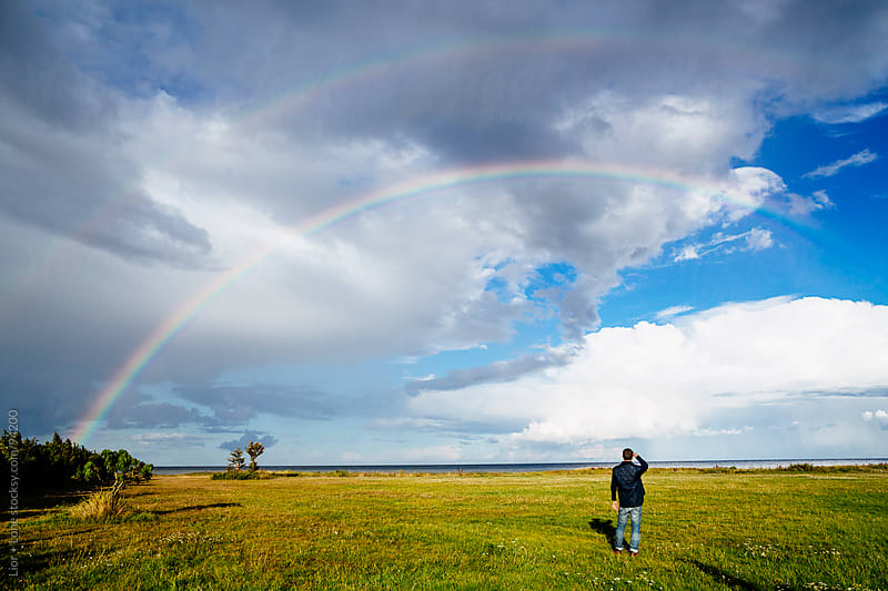 Man standing in a meadow watching rainbow by Lior + Lone for Stocksy United