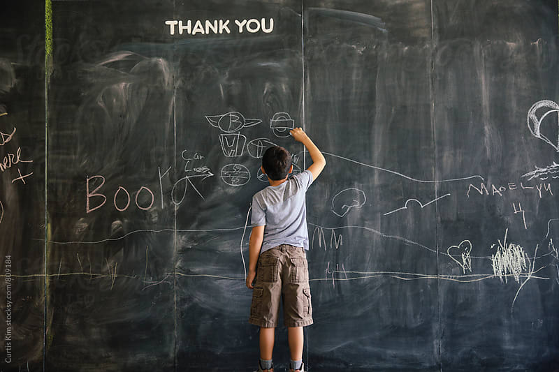 Boy drawing on a large chalkboard paint wall by Curtis Kim for Stocksy United
