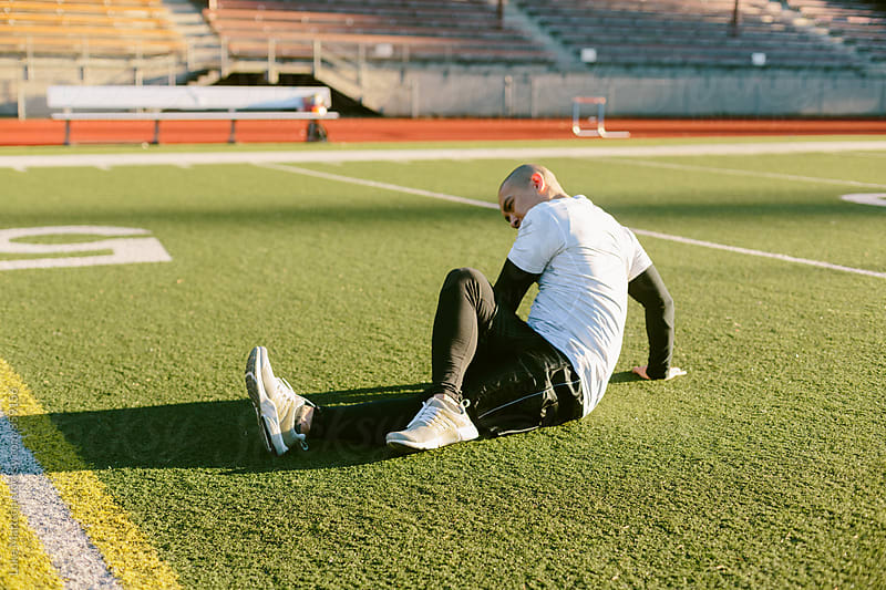 Athletic Man Stretching On Track and Turf Field During Workout by Luke Mattson for Stocksy United