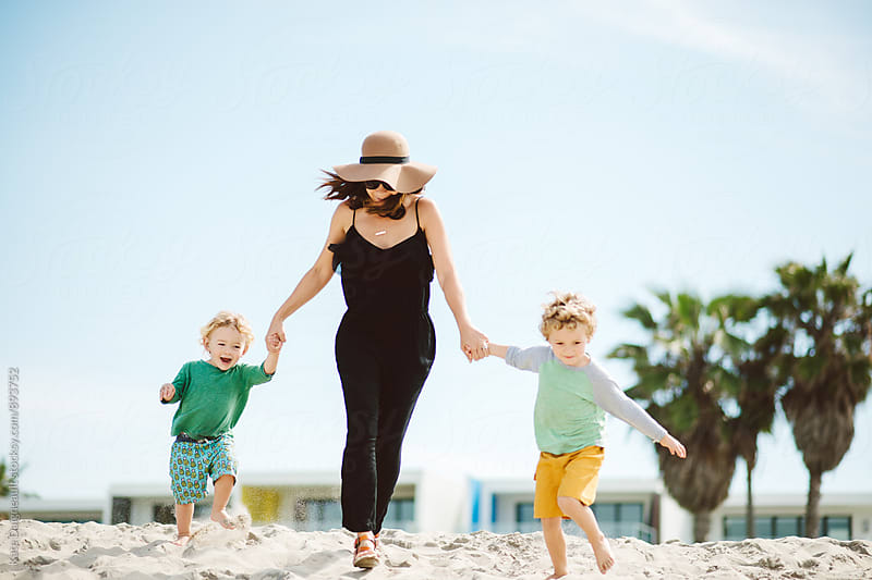 Cute young family running on beach together.  by Kate Daigneault for Stocksy United